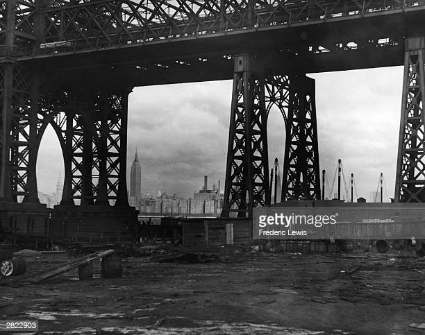 A view of the Williamsburg Bridge taken from under the bridge on the Brooklyn side New York City circa 1950 The Empire State Building is visible in...