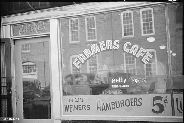 View of the windoe of Farmers Cafe which offers 'Hot Weiners' and hamburgers for 5 cents but has a segregated 'White' only door Durham North Carolina...