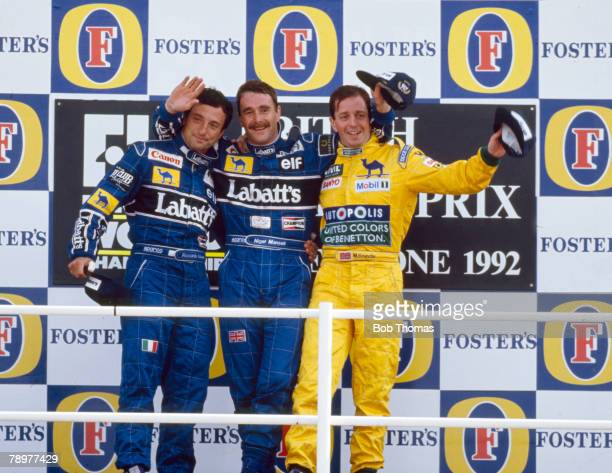 View of the winners of the 1992 British Grand Prix posed together on the podium with from left 2nd placed Riccardo Patrese of Italy first placed...