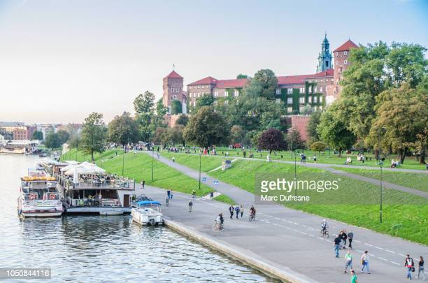 view of the wisla (vistula) river with tour boats and wawel castle in krakow, poland during summer evening - cieszyn stock pictures, royalty-free photos & images