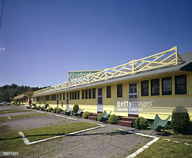 View of the yellow facade of the Vacationland Motel under a blue sky 1960s Each of the groundlevel units features a small plot of grass and a green...
