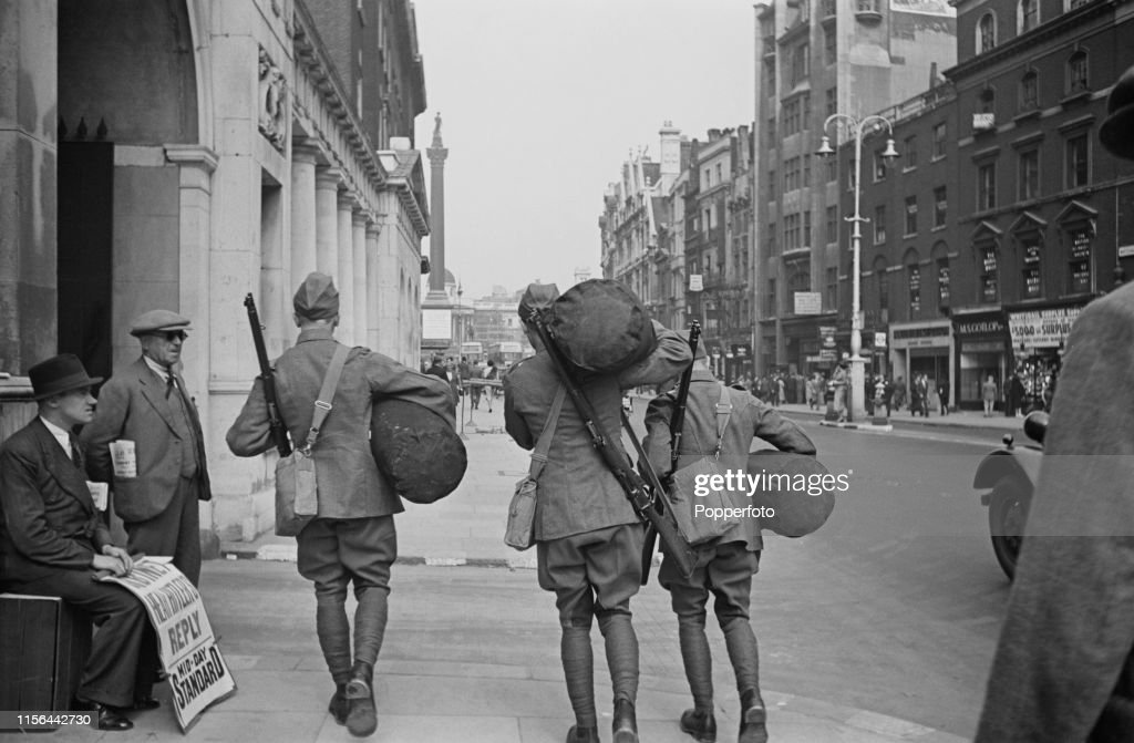 View of three British Army soldiers with kit bags and rifles
