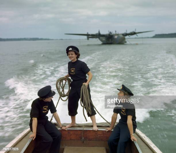 View of three female coxswains of the British Overseas Airways Corporation pictured in the back of a launch after mooring the Boeing 314 Clipper...