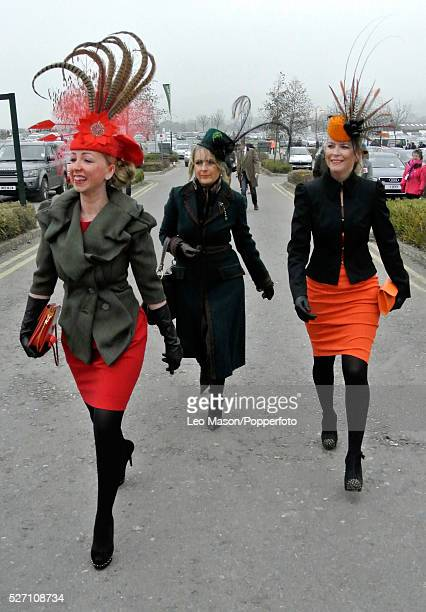 View of three female racing fans and punters wearing exotic hats and fascinators arriving at the course on Ladies Day during the 2012 Cheltenham...