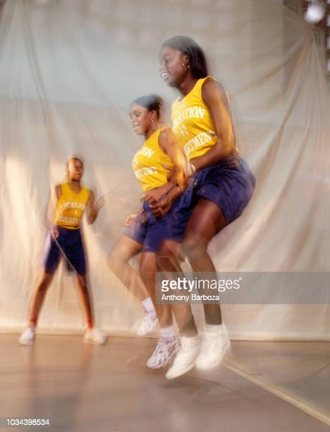 View of three girls as they play double dutch with a pair of jump ropes New York 1990s A fourth player who holds the other ends of the ropes is not...