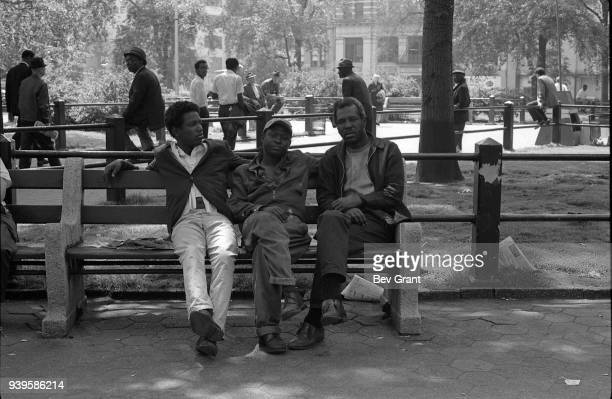 View of three men as they sit together on a bench in Union Square New York New York June 6 1968