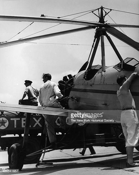 View of three men with an airplane an autogyro getting fuel from a Texaco tank New York 1930