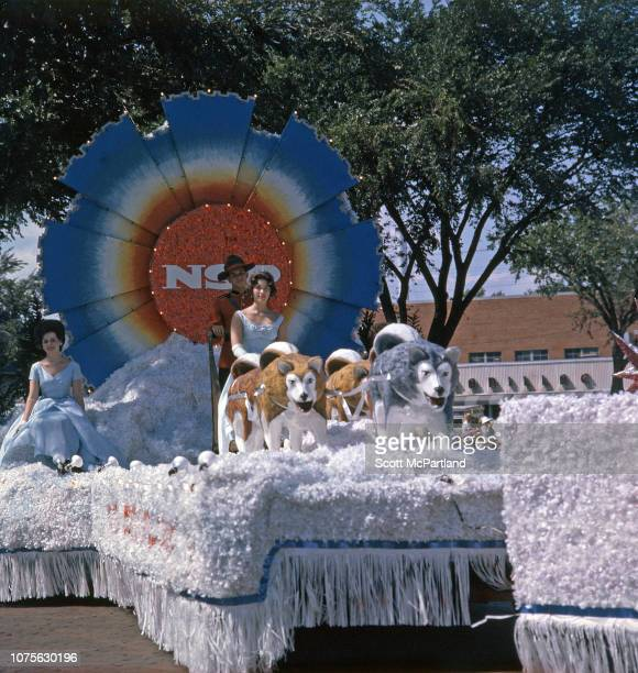 View of three people a man dressed as a Canadian 'mountie' and two women in evening gowns as they ride a winterthemed parade float that features sled...