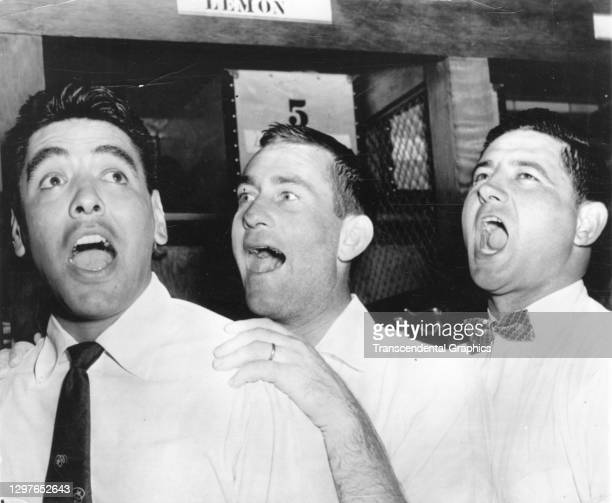 View of three unidentified members of the Cleveland Indians baseball team, all in street cloths, as they sing in the locker room of Municipal...