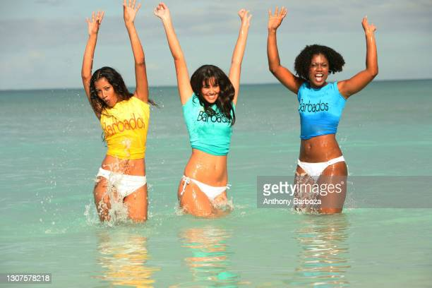 View of three unidentified woman in sleeveless t-shirts and bikini bottoms as they stand, thigh-deep, in the surf, Barbados, April 11, 2008.