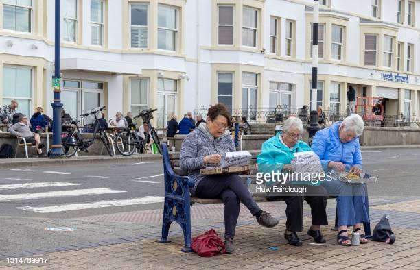 View of three women eating their fish and chips on the Promenade 6 people from different households are now allowed to meet up outside in Wales on...