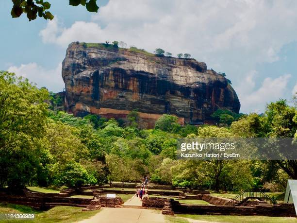 view of tourists on rock formation - sigiriya stock photos and pictures