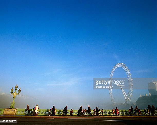 View of tourists walking across Westminster Bridge in the mist