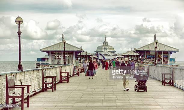 View of tourists walking along the pier at Llandudno, Conwy, North Wales
