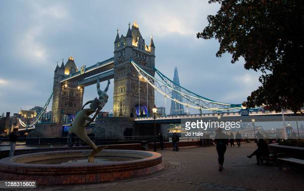 View of Tower Bridge with the Dolphin Statue and the Shard in the background, illuminated in the evening from St Katherines Dock on November 28, 2020...