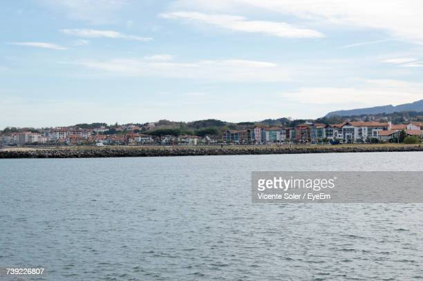 View Of Town By Sea Against Sky