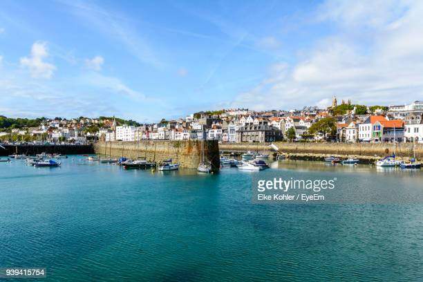 view of town by sea against sky - isola di guernsey foto e immagini stock