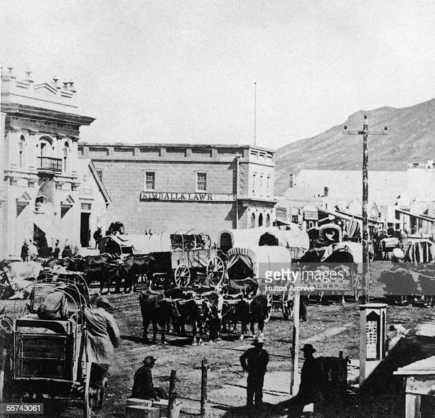 View of traffic along East Temple Street Salt Lake City Utah 1880s A number of covered wagons drawn by cattle are on the unpaved road In the...