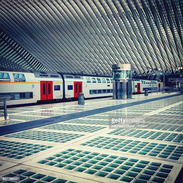 view of train at railway station - liege stock photos and pictures