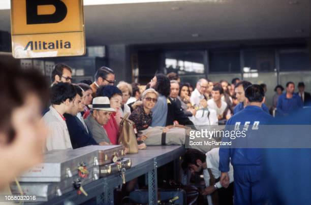 View of travellers crowded at Alitalia airline's baggage claim counter in the passenger terminal of Milan Malpensa Airport Milan Italy August 1968