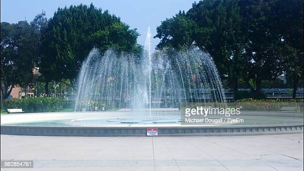 view of trees and fountain in park - fountain stock pictures, royalty-free photos & images