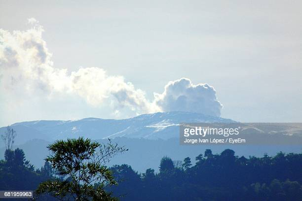 view of trees and mountains against cloudy sky - nevado del ruiz stock photos and pictures