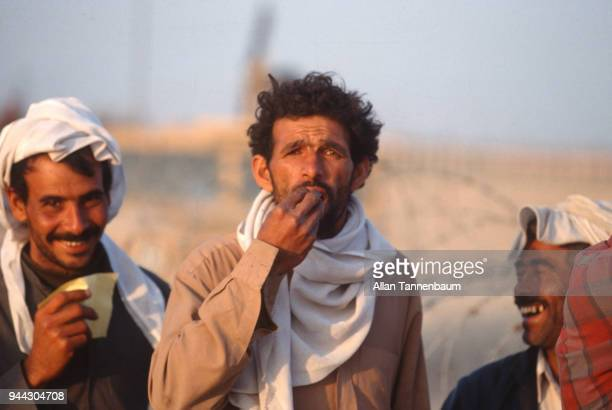 View of trio of Iraqi men at a refugee camp during the Gulf War Iraq 1991 Two of the men laugh as one gestures with his hand in front of his mouth