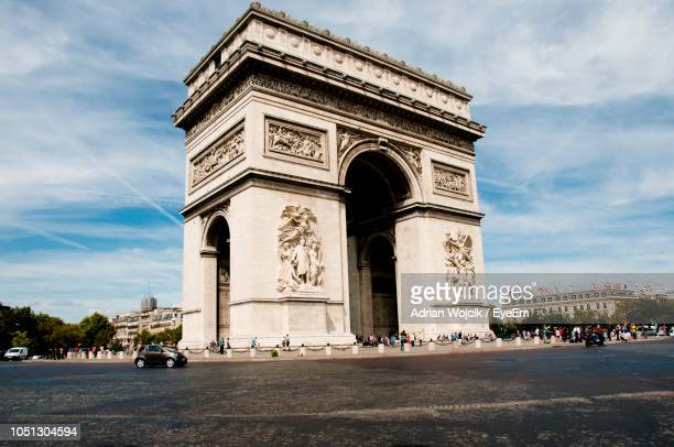 view of triumphal arch against cloudy sky - パリ凱旋門 ストックフォトと画像