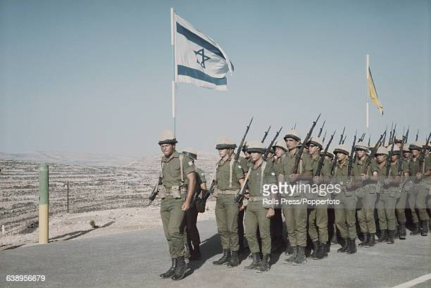 View of troops of the Israel Defense Forces marching along a road past a flag of Israel in the Suez Canal Zone following the occupation of Sinai and...