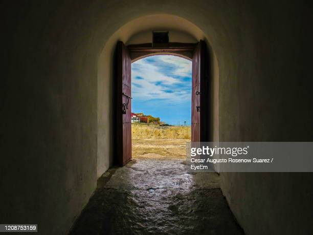 view of tunnel through window of stone wall - man made structure stock pictures, royalty-free photos & images
