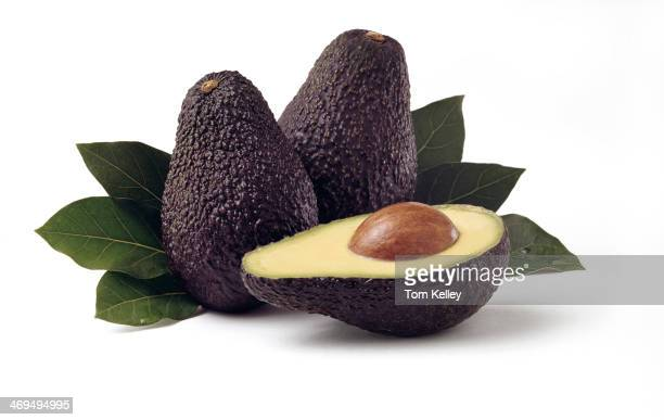 View of two avocados and one half avocado with pit against a background of leaves 2010