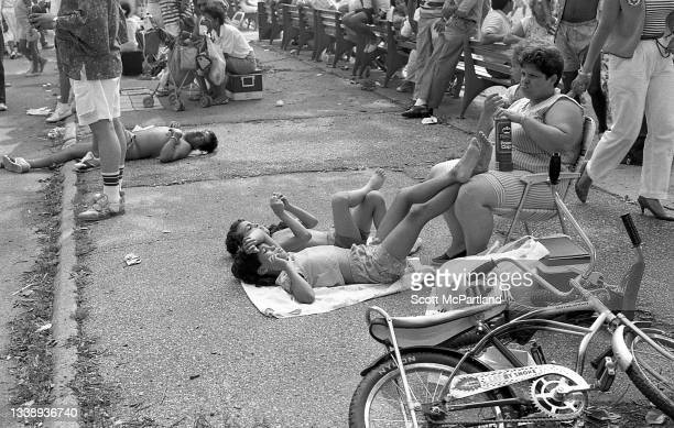 View of two boys lying on the ground, one with his feet resting on the lap a woman who sits in a folding chair, in Flushing Meadows Park, in the...