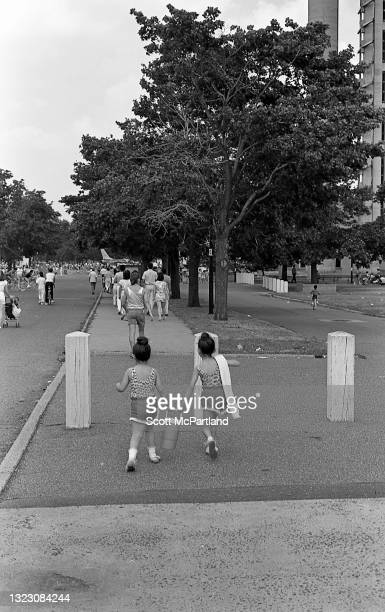 View of two children, both carrying an insulated container, as they enter Flushing Meadows Park, in the Corona neighborhood, Queens, New York, New...
