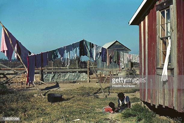 View of two children playing in the backyard of an African American tenant farmer's home in Marcella Plantation Mileston MS in the Mississippi delta...