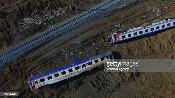 View of two derailed carriages, waiting for removal, after several bogies of a passenger train derailed at the Sarilar village in Corlu district of...