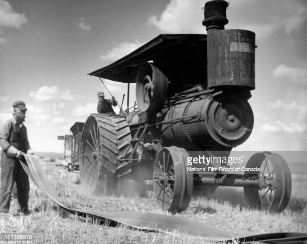 View of two farm workers getting ready to attach the strap to a portable steamengine and threshing machine which was used for shaking the straw and...