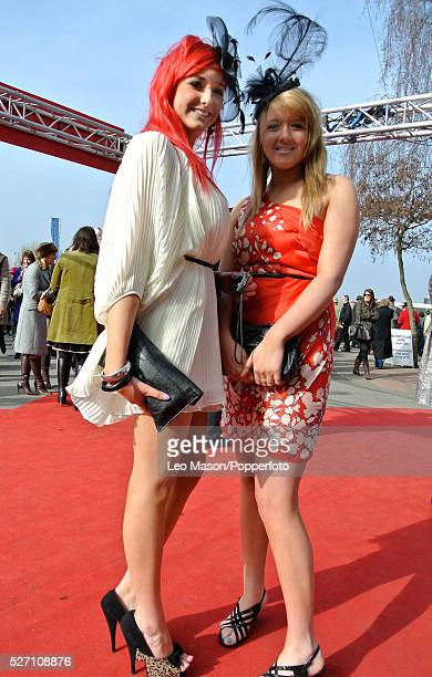 View of two female racing fans pictured wearing summer dresses and fascinators on Ladies Day during the 2012 Cheltenham National Hunt Festival at...