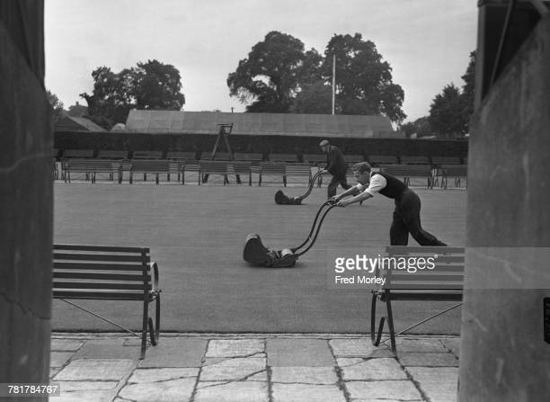 A view of two groundsmen mowing the grass courts in preparation for the Championships on 19 June 1953 at the All England Lawn Tennis and Croquet Club...