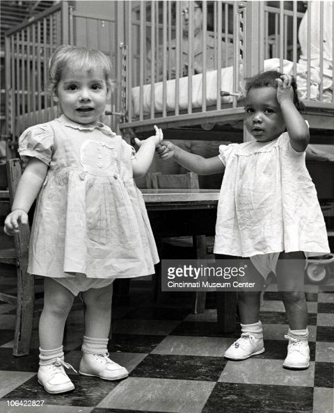 View Of Two Little Girls In Diapers Holding Each Others
