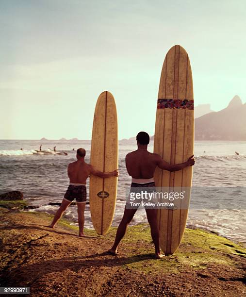 View of two male surfers stand facing the ocean holding their surfboards vertically beside them while watching other surfers on the water California...
