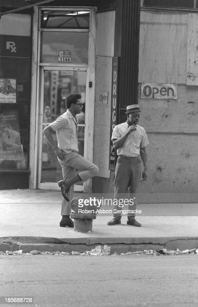 View of two man standing and speaking to each other on a street, Chicago, Illinois, mid 1960s.