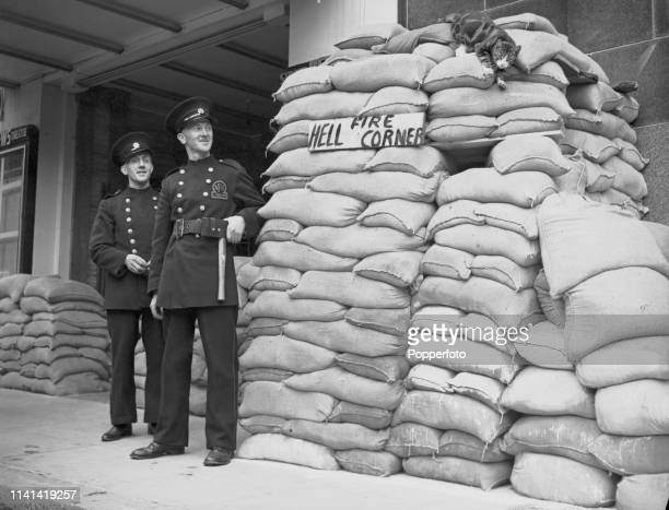 View of two members of the Auxiliary Fire Service watching a cat climb down a sandbag protected AFS post nicknamed Hellfire Corner outside a West End...