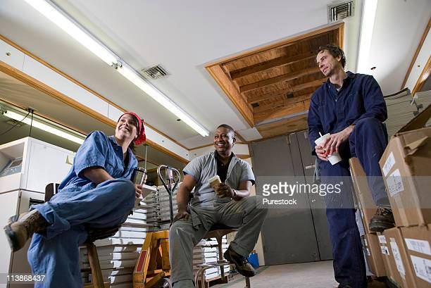 View of two men and a woman enjoying a coffee break while working in a warehouse