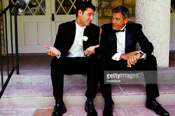 view of two men dressed in tuxedos sitting on the stairs and talking