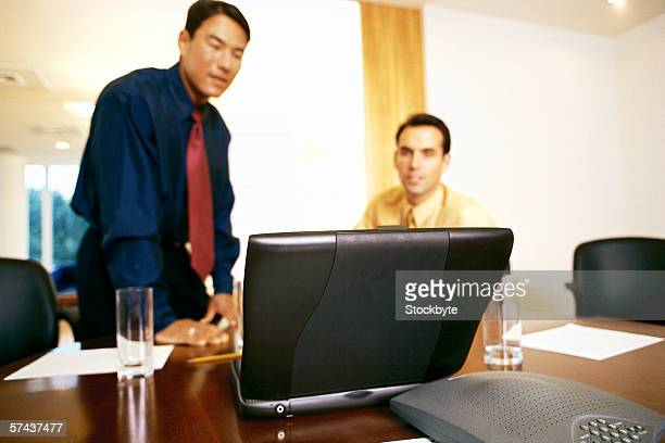 view of two men in an office viewing a computer screen