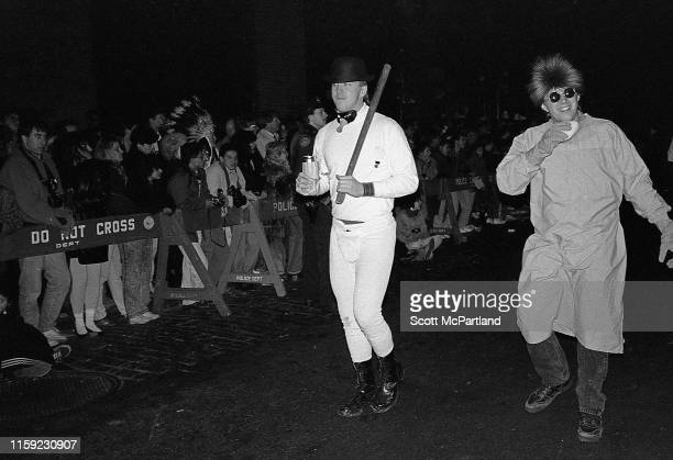 View of two men one dressed as a character from the movie 'A Clockwork Orange' as they walk on 6th Avenue during New York's annual Village Halloween...