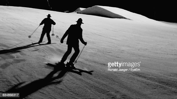 View Of Two Men Skiing Down On Mountain