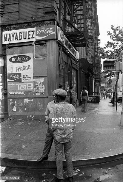 View of two men standing on an unidentified Harlem street corner New York June 1975 Other figures are visible standing outside a storefront possibly...