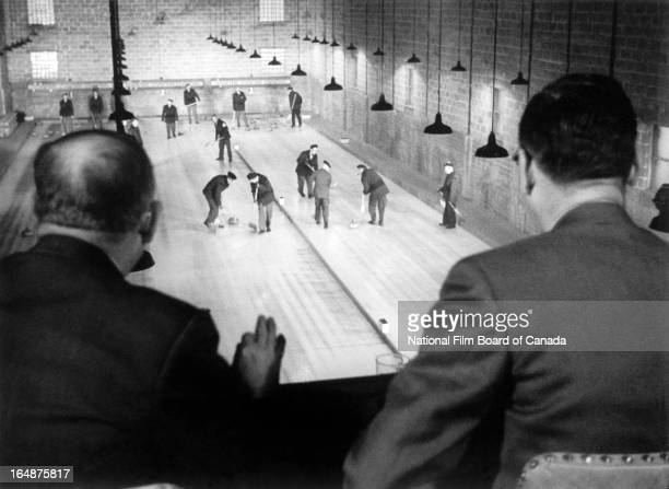 View of two men watching a curling match from the balcony of the local Curling Club in Shawinigan, Quebec, Canada, 1951. Photo taken during the...