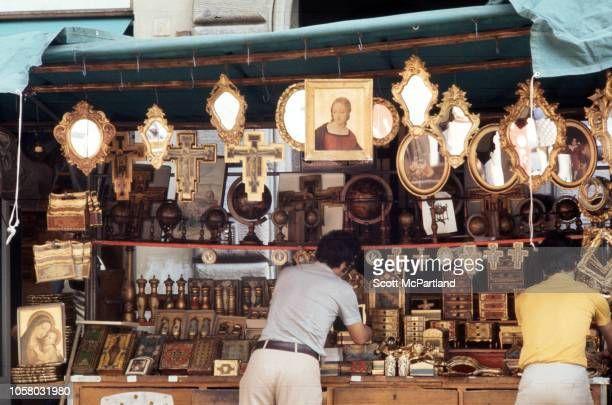 View of two people at a religiouslythemed market stall Florence Italy August 1968